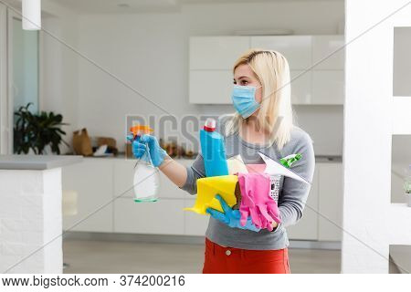 Coronavirus Pandemic. A Disinfector In A Protective Mask Sprays Disinfectants In The Room. Preventio