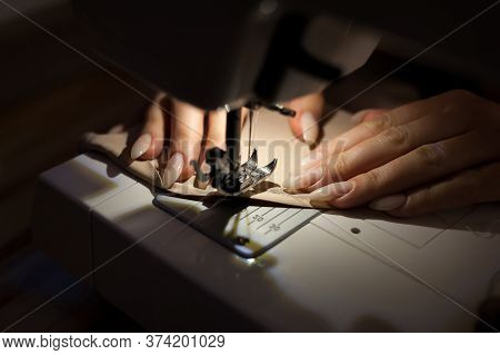 The Woman Is Sewing With Sewing Machine. Sewing Is One Of The Oldest Of The Textile Arts.