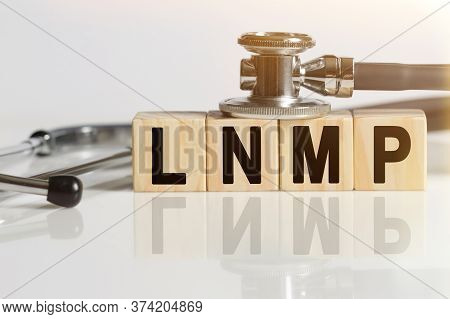 Lnmp The Word On Wooden Cubes, Cubes Stand On A Reflective White Surface, On Cubes - A Stethoscope.