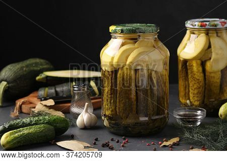 Marinated Cucumbers And Zucchini In Jars On A Dark Background, Harvest For The Winter, Horizontal Fo