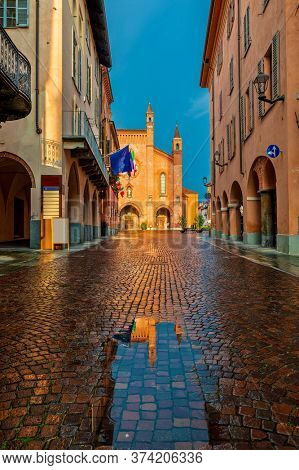 Small puddle on narrow cobblestone street among old houses and San Lorenzo cathedral on background in town of Alba, Piedmont, Northern Italy (vertical composition).
