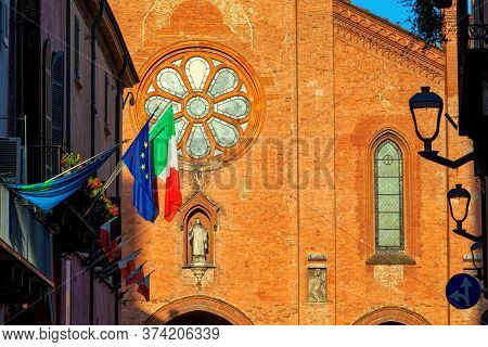 San Lorenzo cathedral (aka Duomo) among old houses in small town of Alba, Piedmont, Northern Italy.