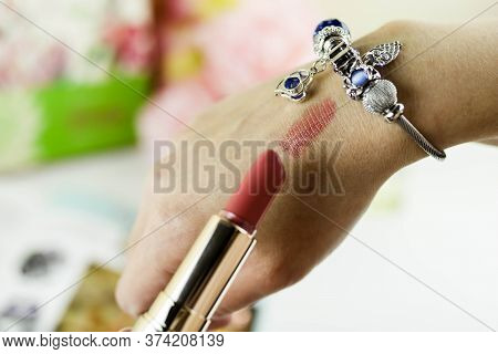Beauty Blogger Doing Lipstick Swatch At Table, Closeup. Lipstick Swatch On Female Hand.