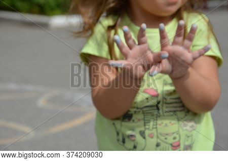 Girl Shows Hands After Drawing, Stained In Chalk. The Child Draws The House With Chalk On The Asphal