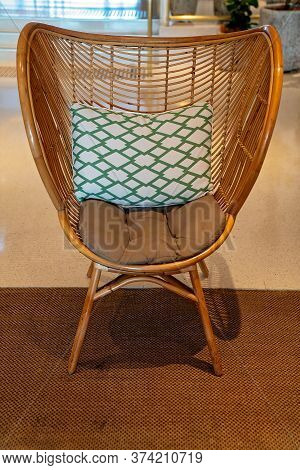 Townsville, Queensland, Australia - June 2020: A Cane Chair With Decorative Cushion In Hotel Foyer