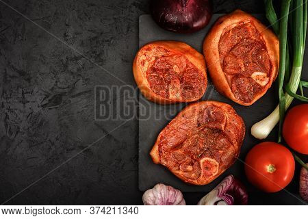 Raw Pork Shank Barbecue Steaks In A Marinade With Fresh Vegetables, Spices, Onions And Garlic On A S
