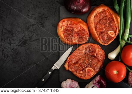 Raw Barbecue Steaks Of Pork Shank In A Marinade With Fresh Vegetables, Spices And A Knife On A Stone