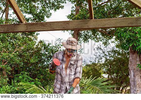Townsville, Queensland, Australia - June 2020: Man Standing Sanding And Repairing Timber Roof Rafter