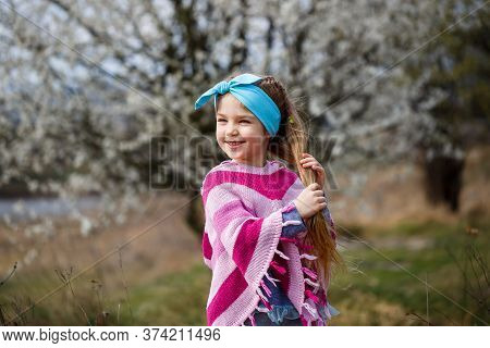 Young Blonde Girl Standing In A Blooming Garden. Blooming Cherry. Portrait Of Beautiful Little Girl.