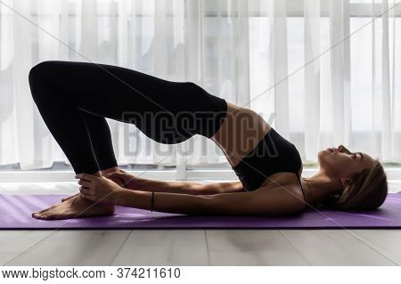 Side View Of Young Woman Doing Gymnastics The Half Bridge Pose In Fitness Studio Or Home Practices Y