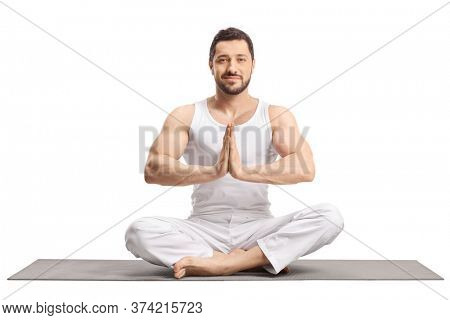 Fit young man in white clothes practicing yoga meditation on the floor isolated on white background