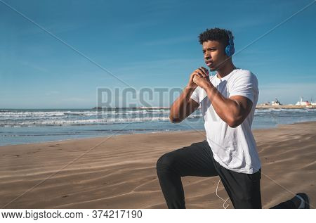 Athletic Man Doing Exercise At The Beach.