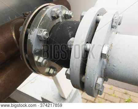Old Grey Painted Rubber Expansion Joint With Cracks In The Pipeline In Industrial Production Line.