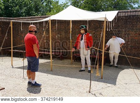Williamsburg, Virginia, U.s.a - June 30, 2020 - A Man In Colonial Costume Assisting Visitors During