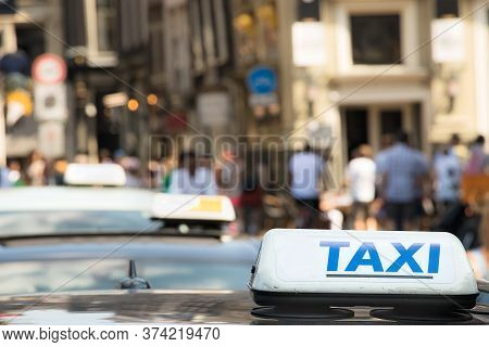 A Taxi Sign With Blue Letter On A Taxi Car In Amsterdam, Netherlands.