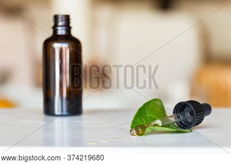 Transparent Glass Dropper With Liquid Spilled Placed On A Green Leaf And A Brown Bottle As A Blur Ba