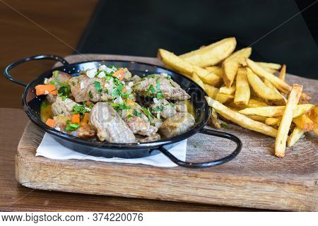 A Pan With Meat, Souce And Vegetables Accompanied With French Fries Potatoes On A Wooden Table.