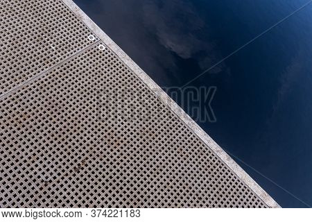 Part Of A Pier And Sky Reflection In The Lake As Geometric Abstract Pattern Background.