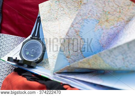 Close Up Picture Of Compass And Map - Preparing For Camping Trip In The Woods
