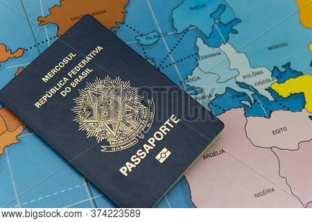 Top View Of Brazilian Passport Over Map. Focus On The European And African Continent. Emigration, Tr