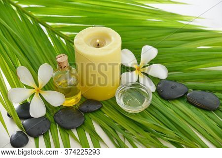 Spa setting with  frangipani and bottles of essential oil ,black stones, candle on green palm background