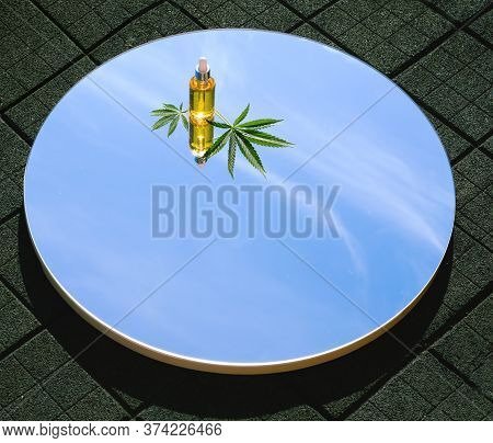 Hemp Oil And Green Cannabis Leaves Are Lying On The Mirror. The Mirror Reflects The Sky. The Mirror
