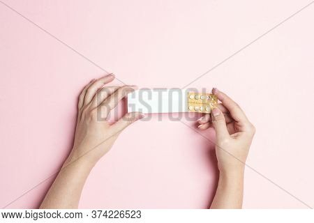 Female Hands Holding Birth Control Pills On Pink Background. Women Contraceptive Hormonal Birth Cont