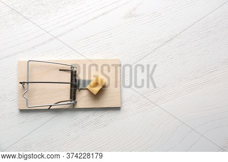 Mousetrap With Piece Of Cheese And Space For Text On White Wooden Background, Top View. Pest Control