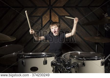 The Child Plays The Drums. Boy Musician Behind A Drum Kit.