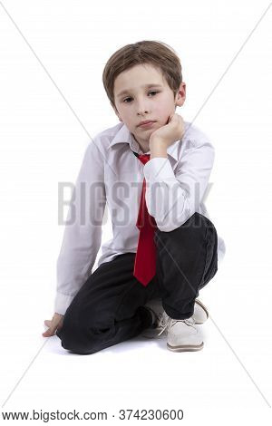 The Child Sits On A White Background. Dressy Boy In A White Shirt Isolated. Seven Year Old Child In