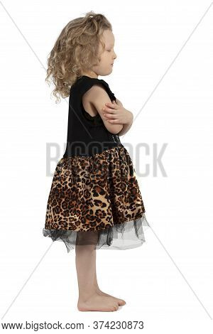 A Little Girl Is Standing Right In Profile. The Little Curly-haired Baby Girl Is Barefoot. Funny Chi