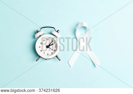 White Lung Cancer Awareness Ribbon And Alarm Clock On Blue Background. November Lung Cancer Awarenes