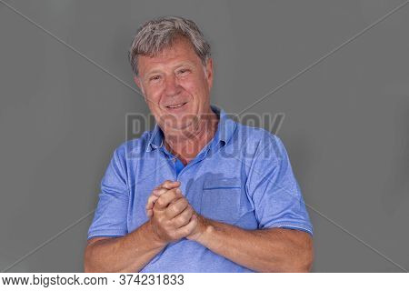 Portrait Of Sixty Year Old Attractive Senior Man In Blue Shirt Isolated On Grey