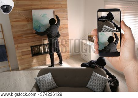 Man Monitoring Situation At His House With Cctv App On Smartphone, Closeup. Thieves Stealing Picture