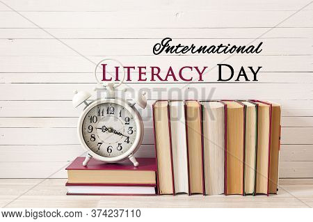 International Literacy Day Concept With Alarm Clock And Pile Of Books On White Wooden Table.