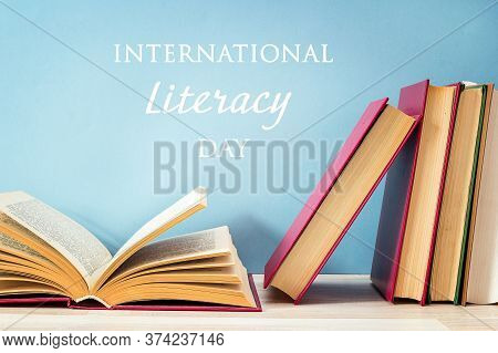 International Literacy Day Concept With Stack Of Books With Open Book On A Blue Background.