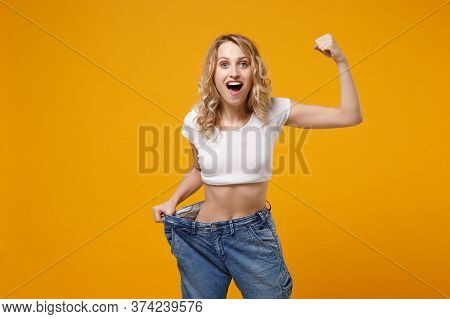 Shocked Woman In White T-shirt Isolated On Orange Background. Proper Nutrition Losing Weight Healthy