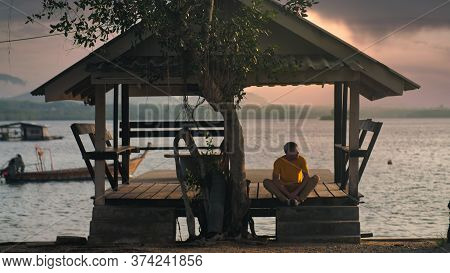 A Handsome Man In Yellow T-shirt Meditate In Arbor In Sunset