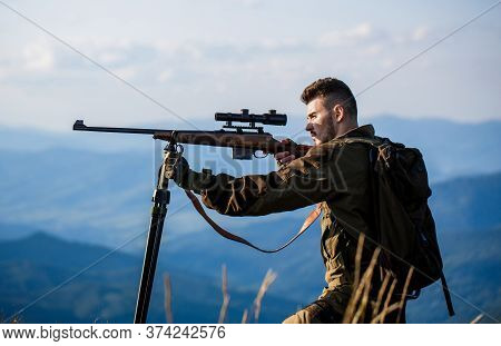 Hunter With Hunting Gun And Hunting Form To Hunt. Hunter Is Aiming. The Man Is On The Hunt. Hunt Hun