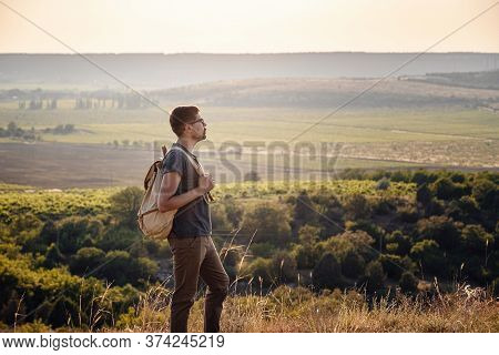 A Man Standing On A Mountain As The Sun Sets.