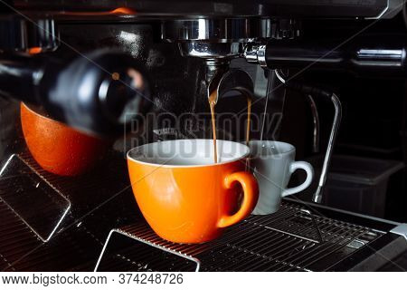 Freshly Brewed Coffee Is Poured From The Coffee Machine Into Cups . Pouring, Beverage.