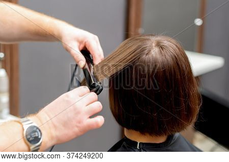Hairdresser Straightens Hair Of Woman With Hair Straightener Tool In Hair Salon.