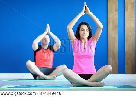 Portrait Of Beautiful Yoga Instructor Teaching Personal Class For Man. Middle-aged Male In Sportswea