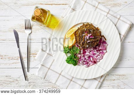 Easy Marinated Wakame Salad With Diced Red Onion, And Lemon Wedges, On A White Plate With Fresh Pars