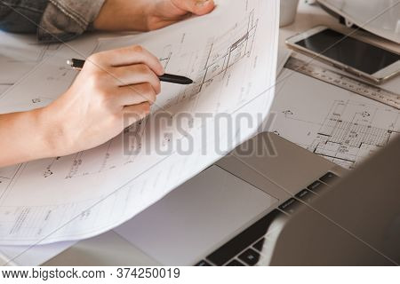 Engineers Holding A Pen Pointing To A Building On A Blueprint And Using A Computer Laptop To  To Pla