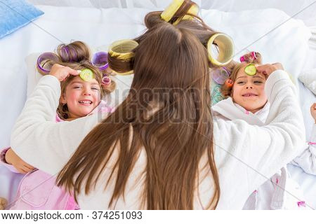 Mother Are Putting Cucumbers On Eyes Of Two Daughters With Curlers In Hair Lying On The Bed In The B