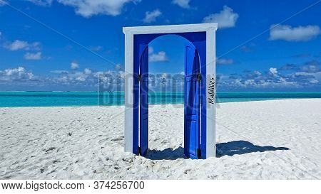 The Door Is Fortunately Open. Sunny Day, On The White Sand Of The Beach Is A Blue Open Door. Ahead I