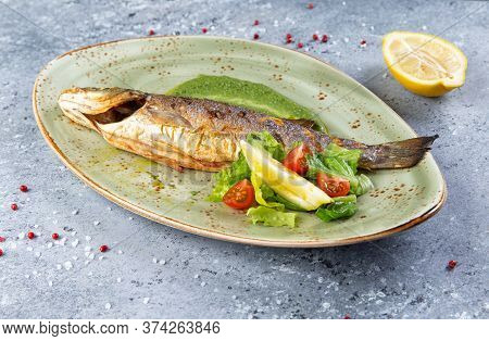 Fried Sea Bass In A Plate On A Gray Background