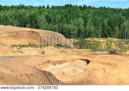 Big Yellow Dump Truck Transporting Stone And Gravel In An Sand Open-pit. Mining Quarry For The Produ