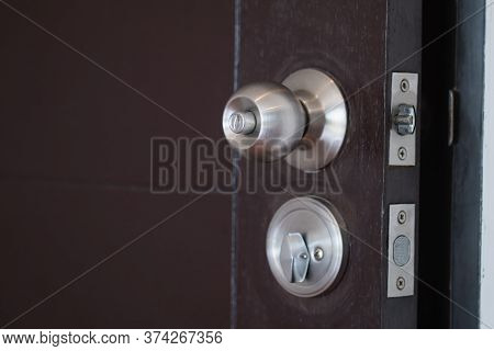 Closeup Stainless Steel Knob, Brown Wooden Door Lock. The Image Is Partially Clear.